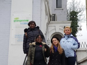 Four women from Haringey Housing Action Group on the steps beside a sign for Grangeview Estates