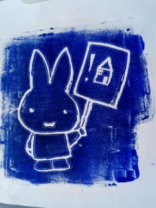 Handmade blue and white engraved print depicting a rabbit holding a placard with a house on it.