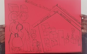 Photo of two hands holding up a placard, drawn in black on red card. There's a drawing of a house full of boxes, with people lifting boxes above their heads. Next to this is a drawing two adults and three children, all with boxes hovering above their heads. At the top it says 'Rehouse The Family In Suitable Accommodation, Support The Homeless'.